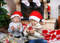 Two little sibling boys being happy about christmas present playing with toys indoor with decoration Stock Photos