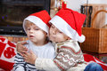 Two little sibling boys being happy about christmas present portrait of boy in santa hats indoor with decoration Stock Images