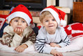 Two little sibling boys being happy about christmas present portrait of in santa hats indoor with decoration Royalty Free Stock Photo