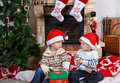 Two little sibling boys fighting about christmas present indoor with decoration Stock Images