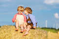 Two little sibling boys and friends sitting on hay stack or bale speaking yellow wheat field in summer Royalty Free Stock Image