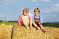 Two little sibling boys and friends sitting on hay stack speaking yellow wheat field in summer Royalty Free Stock Images