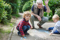 Two little sibling boys and happy grandfather painting with chal chalk outdoors in summer selective focus on boy Royalty Free Stock Image
