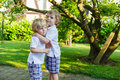Two little sibling boys having fun outdoors in family look summer Stock Image