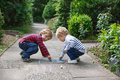 Two little sibling boys painting with chalk outdoors in summer Stock Image