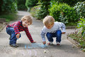 Two little sibling boys painting with chalk outdoors in summer Stock Photo
