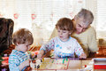 Two little sibling boys playing with grandfather board game indoors Stock Images