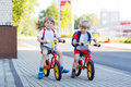 Two little siblings children having fun on bikes in city outdoo boys vacations outdoors Royalty Free Stock Photos