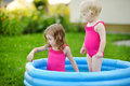 Two little siblings sisters having fun with water in summer garden Stock Photo