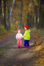 Two little sister walk in the oak grove sunny autumn day Stock Image