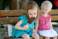 Two little sisters eating ice cream outdoors Royalty Free Stock Photos