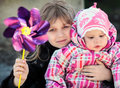 Two little sisters outdoor portrait with pinwheel toy Royalty Free Stock Image