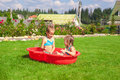 Two little sisters playing and splashing in the Stock Photography