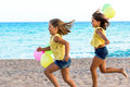 Two little sisters running together on beach. Royalty Free Stock Photo