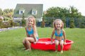 Two little sisters sitting in their yard in small frolicing and splashing pool Stock Photos