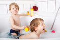Two little twins boys having fun with water by taking bath in ba adorable twin bathtub Stock Photo