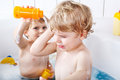Two little twins boys having fun with water by taking bath in ba adorable twin bathtub Royalty Free Stock Photos