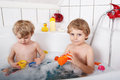 Two little twins boys having fun with water by taking bath in ba bathtub Stock Photography