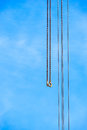 Two long chains with hooks next to four cables on sky