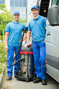 Two Male Cleaners With Vacuum Cleaner Royalty Free Stock Photo
