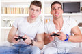 Two male friends playing video game with controllers Royalty Free Stock Photo