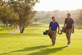 Two Male Golfers Walking Along Fairway Carrying Bags Royalty Free Stock Photo