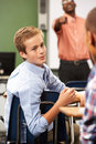 Two male pupils talking in class with teacher telling them off raising arm Royalty Free Stock Images