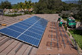 Two male solar workers install solar panels on home in oak view southern california Royalty Free Stock Images