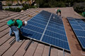 Two male solar workers install solar panels on home in oak view southern california Royalty Free Stock Photo