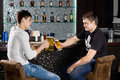 Two male teenagers sitting at the bar toasting happy holding glasses of beer with shelves with bottles of alcoholic beverages iin Royalty Free Stock Image