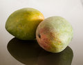 Two mangoes on reflecting surface Stock Photos