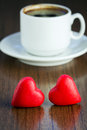 Two marzipan red candy and cup of black coffee for valentine s day Stock Photo