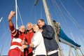 Two mature couples standing on deck of yacht moored at harbour jetty posing for group photograph senior man taking self portrait Stock Photos