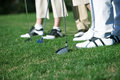 Two mature couples standing on golf course, focus on golf shoes, clubs and grass, side view, low section (surface level) Royalty Free Stock Photo