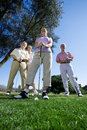 Two mature couples standing on golf course smiling front view portrait surface level Royalty Free Stock Photo
