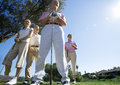 Two mature couples standing on golf course smiling front view portrait surface level lens flare Stock Images