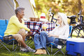 Two mature women relaxing on camping holiday smiling Royalty Free Stock Photo