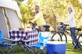 Two mature women riding bikes on camping holiday smiling to camera Royalty Free Stock Photo