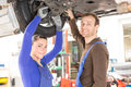 Two mechanics repairing inspecting car hydraulic lift Royalty Free Stock Image