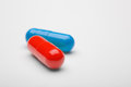 Two medical pills blue and red with a shadows Royalty Free Stock Photo