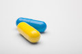 Two medical pills blue and yellow with a shadows Royalty Free Stock Photo