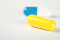 The two medical pills yellow and blue Royalty Free Stock Photo