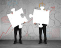 Two men assembling puzzles with business doodles background Royalty Free Stock Photo