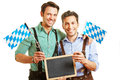 Two men in bavaria with empty smiling chalkboard and flags Royalty Free Stock Photo