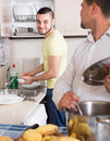 Two men cooking at home smiling male friends and doing dishes kitchen Stock Photo