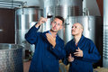 Two men coworkers wearing uniform standing with glass of wine Royalty Free Stock Photo