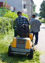 Two men are cutting grass Stock Images