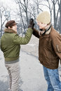 Two men doing high five in park young meeting winter giving Stock Photo