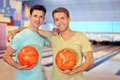 Two men embrace and hold balls in bowling club Royalty Free Stock Images