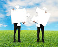 Two men holding blank puzzles on grass ground Royalty Free Stock Photo